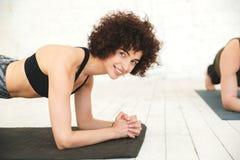 Tavolato sorridente della donna di forma fisica su una stuoia di esercizio Fotografia Stock