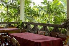 Tavole e copertura di legno delle sedie dalla tovaglia rossa nel giardino Immagine Stock Libera da Diritti