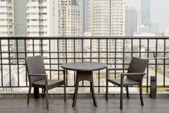 Tavole e sedie vuote al terrazzo con l'alta vista della costruzione Immagini Stock