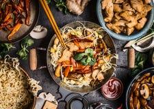 Tavolo da cucina asiatico con le ciotole dell'alimento, il wok, la frittura di scalpore, i bastoncini e gli ingredienti su fondo Fotografia Stock