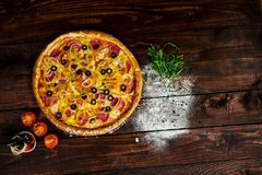 Tavolo da cucina di legno con pizza spruzzata con farina immagini stock