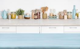 Tavolo da cucina di legno vuoto blu sopra il fondo vago degli ingredienti alimentari Fotografia Stock