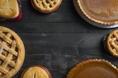 Tavolo da cucina in pieno delle torte differenti, torte di zucca, torte di mele, con spazio vuoto nel mezzo Dessert tradizionale  fotografia stock libera da diritti