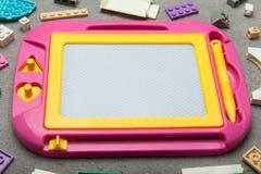 Tavolo da disegno magnetico su un fondo blu con i giocattoli Giocattoli educativi fotografia stock