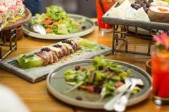 Tavolo da pranzo con le insalate sui piatti ceramici, fuoco selettivo Un ristorante fotografia stock