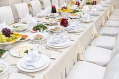 Tavolo da pranzo festivo servito con i piatti sui piatti, sedie, veget Fotografia Stock Libera da Diritti