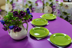 Tavolo da pranzo porpora con i piatti verdi Fotografie Stock