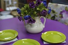 Tavolo da pranzo porpora con i piatti verdi Immagini Stock
