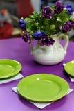 Tavolo da pranzo porpora con i piatti verdi Fotografia Stock Libera da Diritti