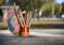 Tavolozza, colori e spazzole dell'artista sullo scaffale Fotografia Stock Libera da Diritti