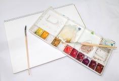 Tavolozza con le spazzole sul libro Fotografia Stock