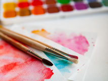 Tavolozza delle pitture, delle spazzole e della carta dell'acquerello per un colo dell'acqua Fotografie Stock
