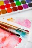 Tavolozza delle pitture, delle spazzole e della carta dell'acquerello per un colo dell'acqua Fotografia Stock