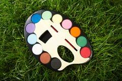 Tavolozza di arte con pittura su un'erba verde Fotografie Stock Libere da Diritti