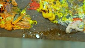 Tavolozza di legno di arte con le pitture ad olio Colori di miscelazione insieme, primo piano, 4k stock footage