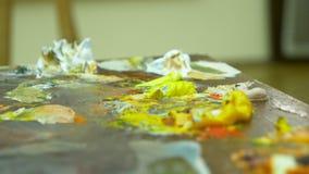 Tavolozza di legno di arte con le pitture ad olio Colori di miscelazione insieme, primo piano, 4k video d archivio