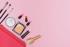 Tavolozza e spazzole dei cosmetici di trucco sulla disposizione rosa del piano del fondo Fotografie Stock
