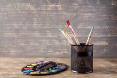 Tavolozza e vaso dell'acquerello con le spazzole Fotografia Stock Libera da Diritti