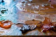 Tavolozza utilizzata del ` s dell'artista con i colori misti del primo piano delle pitture acriliche come fondo di arte Fotografia Stock Libera da Diritti