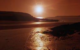 Tawny Sunset, através da praia e do mar do ângulo fotografia de stock royalty free