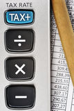 TAX. Detail of calculator, focusing the TAX key, next to a sheet of paper with numbers and a pencil Stock Photos
