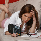 Tax. A young woman holding a calculator, doing her taxes Stock Photography
