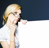 Tax Accountant Holding Blank Sign Board. Picture of a cute blonde female tax accountant in glasses holding blank sign board to display information about Royalty Free Stock Photos