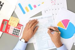 Tax accountant working with documents. At table stock photo