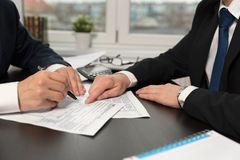 Tax advisor helps to complete US 1040 tax form stock images