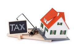 Tax as a mousetrap. Miniature house in mousetrap of taxes, concept Stock Photography