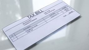 Tax bill lying on white table, payment for services, month expenses, tariff. Stock photo stock illustration