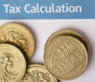 Tax calculation. A heap of British pound coins, showing the Welsh leek and the coat of arms of the UK, on a British tax office form Stock Photography