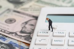 Tax calculation or tax refund for individual or company concept, miniature businessman leader standing and thinking with tax plus. Button on calculator and pile stock images