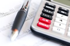 Tax calculator and pen. Calculating numbers for income tax return with pen and calculator Royalty Free Stock Images