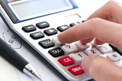 Tax calculator and pen. Typing numbers for income tax return with pen and calculator