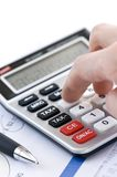 Tax calculator and pen. Typing  numbers for income tax return with pen and calculator Stock Photo