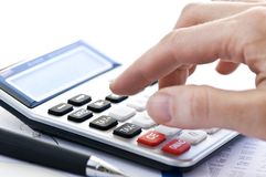 Tax calculator and pen. Typing  numbers for income tax return with pen and calculator Royalty Free Stock Photo