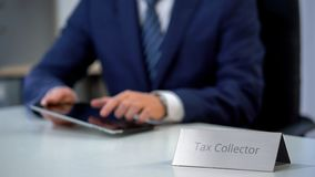 Tax collector using tablet pc with database of debtors with bad credit history. Stock photo stock photos