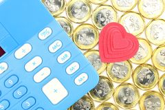 Tax or cost calculation. Calculator on gold , and silver coins  with heart shape object.  Concept for passion on tax , cost , budget , bill , profit ,revenue Stock Photos