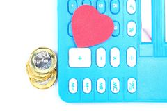 Tax or cost calculation. Calculator with  gold , and silver coins  with heart shape object.  Concept for passion on tax , cost , budget , bill , profit ,revenue Royalty Free Stock Photo