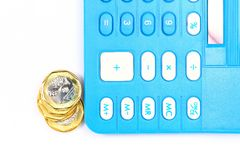 Tax or cost calculation. Gold , and silver coins beside calculator.  Concept for tax , cost , budget , bill , profit ,revenue calculation etc Stock Image