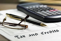 Tax and credits. Concept. Getting refund from the income tax return. Calculator, glasses and black pen on financial documents royalty free stock photos