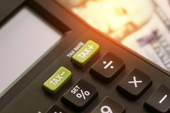 Tax cuts or reduce concept, selective focus on TAX minus buttons. On calculator with background of blurred US Dollar banknotes, United States government tax stock images