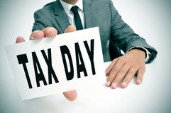 Tax day. A businessman sitting in a desk showing a signboard with the text tax day written in it Royalty Free Stock Image