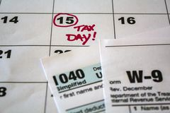 Tax day marked on calendar and tax forms royalty free stock photo