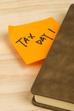 Tax day note and notebook. Close up of a post-it note saying tax day and a notebook on wooden background Royalty Free Stock Photos