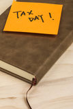 Tax day note and notebook. Close up of a post-it note saying tax day and a notebook on wooden background Stock Photos