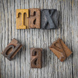 Tax Day Spelled out in Wood Block Letters on Wood Background Stock Photography