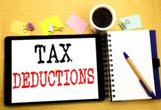 Tax Deductions. Business concept for Finance Incoming Tax Money Deduction Written on tablet laptop, wooden background with sticky. Tax Deductions. Business Stock Photography
