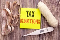 Tax Deductions. Business fitness health concept for Finance Incoming Tax Money Deduction written sticky note empty paper backgroun. Tax Deductions. Business Stock Photography